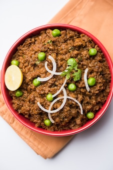 Baranina kheema pav lub indyjskie pikantne mięso mielone podawane z chlebem lub kulcha, przyozdobione zielonym groszkiem. nastrojowe tło. selektywne skupienie