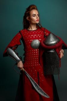 Barbarzyńca żeński wojownik pozuje z hełmem i nożem
