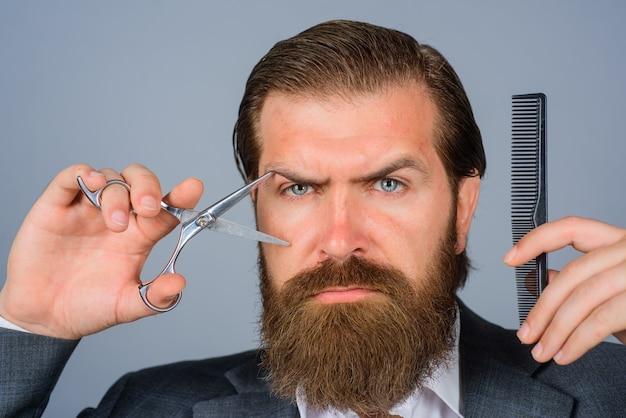 Barbershop brodaty mężczyzna z nożyczkami i grzebieniem fryzjer brodaty mężczyzna z profesjonalnymi narzędziami fryzjerskimi