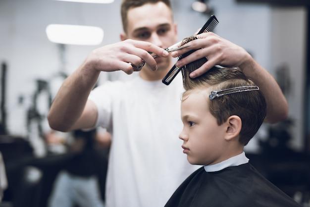 Barbershop hairdresser make boy haircut