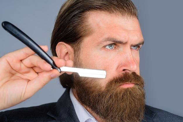Barbershop salon fryzjerski dla mężczyzn fryzjer z bliska portret brodatego mężczyzny z przystojnym brzytwą