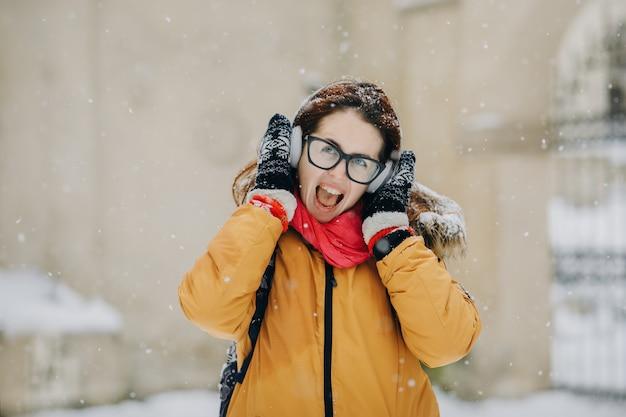 Bardzo atrakcyjny dziewczyna hipster w zimie. ona słucha muzyki na słuchawkach. moda uliczna dla młodzieży. zimowa zabawa spacery na świeżym powietrzu