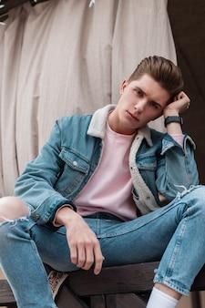 Bardzo atrakcyjny młody człowiek w modnej kurtce dżinsowej w vintage t-shirt w modnych dżinsach lubi relaks na świeżym powietrzu. przystojny nowoczesny facet w dżinsach ubrania na ulicy. codzienny wygląd młodości. zwyczajny styl.