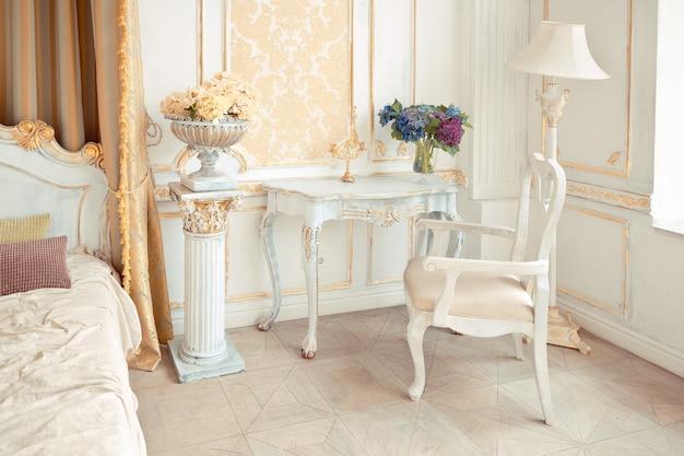 Bardzo bogate wnętrze mieszkania ze złotymi zdobieniami na ścianach w stylu barokowym i luksusowymi meblami ze złotą farbą.