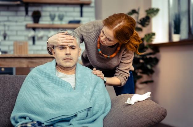 Bardzo chory. przyjemna niespokojna kobieta czuje temperaturę męża, martwiąc się o niego