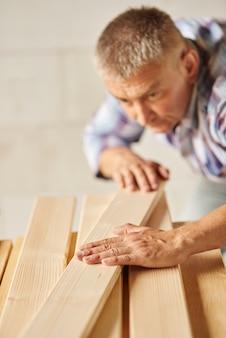 Bardzo ciężko pracujący mężczyzna kładzie kolejne drewniane deski