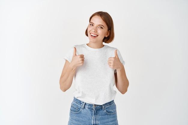 Bardzo dobra, fajna robota. uśmiechnięta dziewczyna mówi tak, pokazując kciuki w górę z aprobatą, lubi i zgadza się, komplementuje, stojąc na białej ścianie