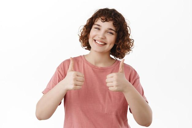 Bardzo dobra, fajna robota. uśmiechnięta młoda krągła dziewczyna pokazująca kciuk w górę, dająca pozytywne opinie, polecająca coś fajnego, chwaląca świetną robotę, stojąca na białym