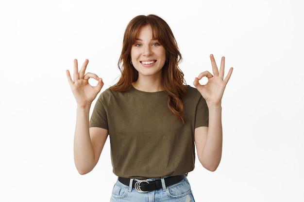 Bardzo dobrze, dobra robota. uśmiechnięta młoda kobieta pokazująca ok, ok gest, kiwa głową z aprobatą, mówi tak, zgadza się z wyborem, chwali wspaniałą rzecz, stojąc na białym