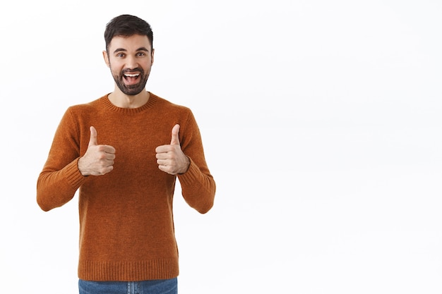 Bardzo dobrze, idź dalej. portret szczęśliwego, wesołego brodatego mężczyzny pokazuje kciuki w górę i uśmiecha się, kiwa głową, zachęca osobę, chwali osiągnięcia, zatwierdza i lubi pomysł, biała ściana