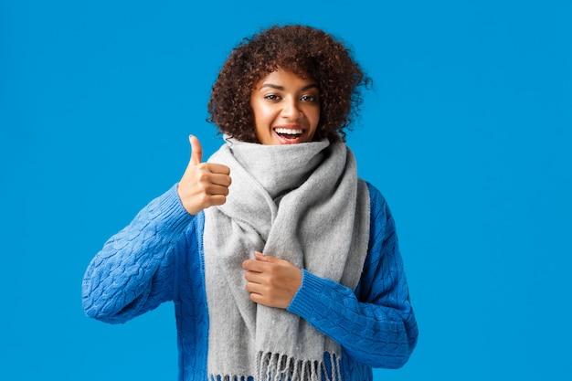 Bardzo dobrze tak. śliczna szczęśliwa afroamerykańska kobieta w swetrze, kupiona chłodno ciepła