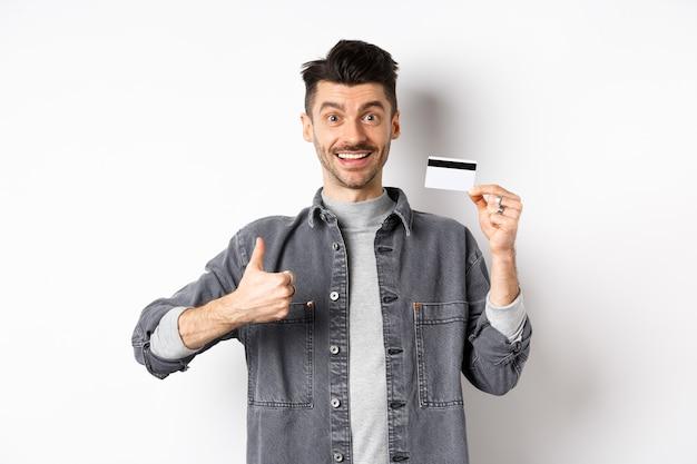 Bardzo dobrze. uśmiechnięty facet z plastikową kartą kredytową pokazujący kciuki do góry, uśmiechnięty zadowolony, polecający bank, stojący na białym tle.