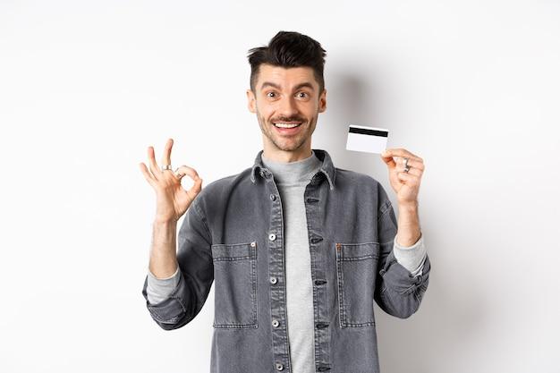 Bardzo dobrze. uśmiechnięty facet z plastikową kartą kredytową pokazujący znak dobra, uśmiechnięty zadowolony, polecający bank, stojący na białym tle.