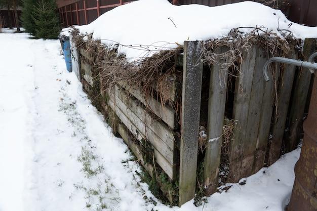 Bardzo duży trzyczęściowy drewniany kompostownik stojący w ogrodzie zimą na wsi do ekologicznego kompostowania żywności i odpadów ogrodowych