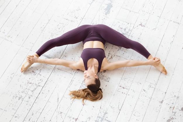 Bardzo elastyczna młoda kobieta w ciemnym bordowym stroju sportowym, uprawiająca jogę z rozcięciem z przodu