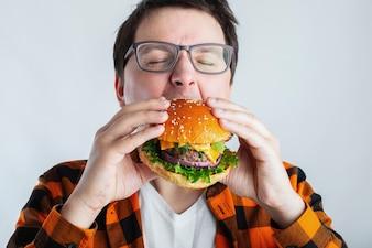Bardzo głodny uczeń je fast food.