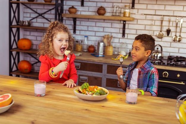 Bardzo głodny. piękna dziewczyna z kręconymi włosami trzymająca otwarte usta podczas jedzenia warzyw