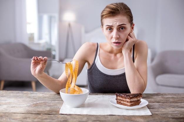 Bardzo głodny. przygnębiona młoda kobieta siedzi przy stole na diecie