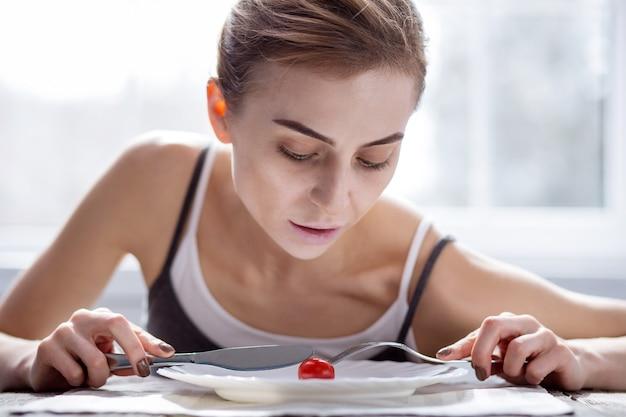 Bardzo głodny. smutna młoda kobieta siedzi przy stole podczas posiłku