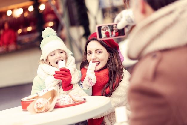Bardzo głodny. zachwycone kobiety jedzące słodycze spędzając razem czas na jarmarku bożonarodzeniowym