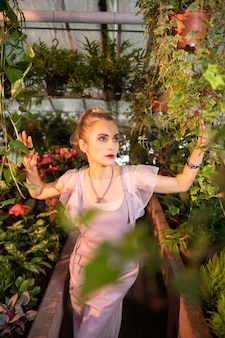 Bardzo ładny. atrakcyjna sympatyczna kobieta stojąca wśród zielonych roślin i podziwiająca ich piękno
