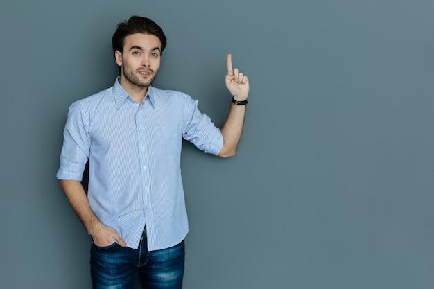 Bardzo mądry. ładny, inteligentny przystojny mężczyzna, wskazując palcem w górę i patrząc na ciebie, dzieląc się swoim pomysłem