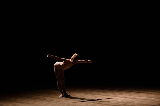 Bardzo młoda balerina pozuje na czarnym tle
