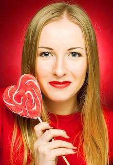 Bardzo młoda blond kobieta trzyma lollypop