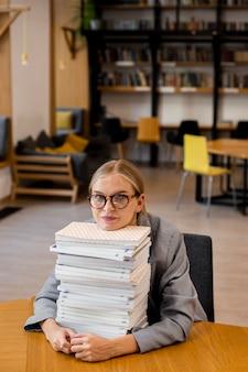Bardzo młoda dziewczyna pozuje w bibliotece