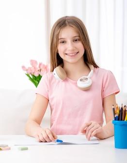 Bardzo młoda dziewczyna studiuje podczas noszenia słuchawek