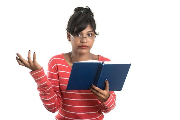 Bardzo młoda dziewczyna trzyma książkę i pozowanie na białej ścianie