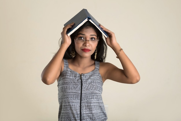 Bardzo młoda dziewczyna trzyma książkę i pozuje