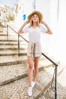 Bardzo młoda dziewczyna w kapeluszu spacery po schodach na zewnątrz w lato ulicy.