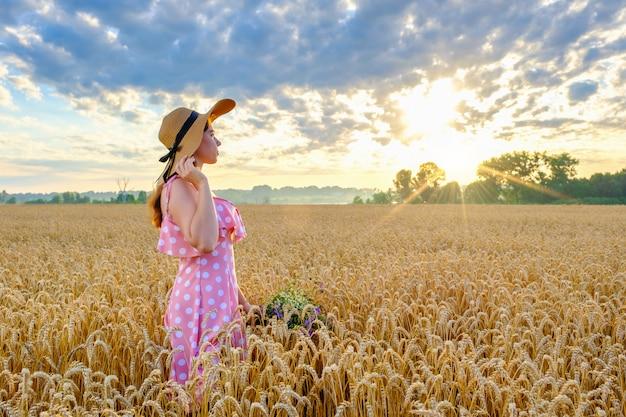 Bardzo młoda dziewczyna z długimi włosami wygląda na słońce i trzyma bukiet dzikich kwiatów w polu pszenicy o wschodzie słońca.