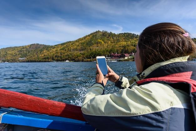 Bardzo młoda kobieta biorąc zdjęcie na smartfonie żeglowanie po jeziorze bajkał na łodzi
