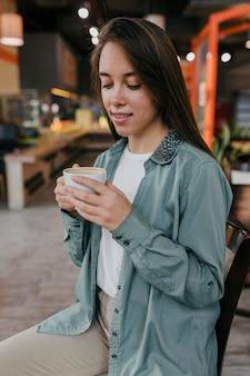 Bardzo młoda kobieta, ciesząc się filiżanką kawy