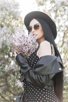 Bardzo młoda kobieta i niesamowity bukiet kwiatów bzu w ogrodzie. atrakcyjna dziewczyna w czarnym stroju w okularach przeciwsłonecznych w eleganckim kapeluszu obejmuje twarz piękne kwiaty w parku. zmysłowy świeży portret urocza dama.