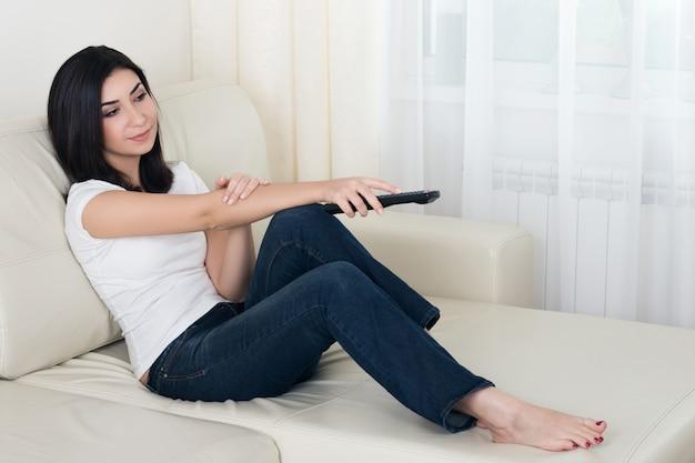 Bardzo młoda kobieta oglądając telewizję i zmieniając kanały na kanapie