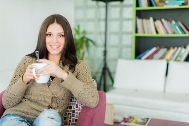 Bardzo młoda kobieta pije herbatę