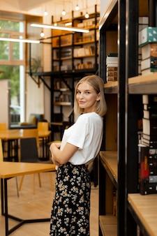Bardzo młoda kobieta pozuje w bibliotece