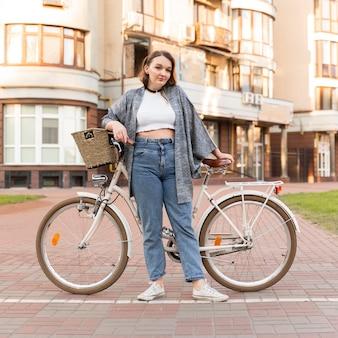 Bardzo młoda kobieta pozuje z rowerem