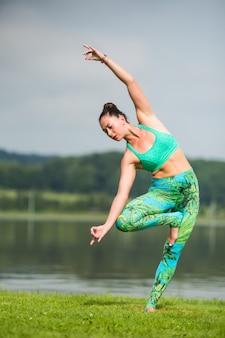 Bardzo młoda kobieta robi ćwiczenia jogi w parku