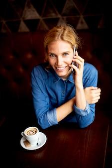 Bardzo młoda kobieta siedzi przy stole z kawą lub cappuccino i przy użyciu telefonu komórkowego