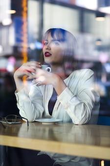 Bardzo młoda kobieta spędza czas w restauracji przy filiżance kawy. strzał przez szybę w oknie