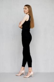 Bardzo młoda kobieta stojąca w profilu ze skrzyżowanymi rękami na piersi
