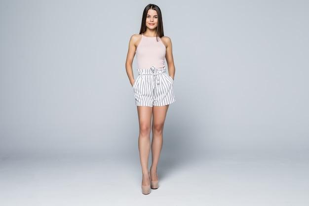 Bardzo młoda kobieta stwarzających w sexy jeansowe szorty, na białym tle na białym w pełnej długości