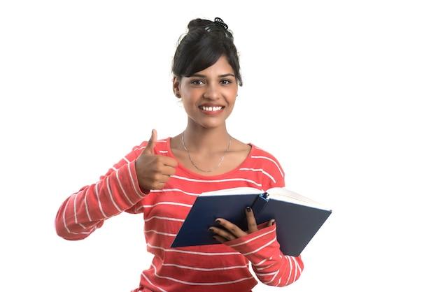 Bardzo młoda kobieta trzyma książkę i pozowanie na białym tle