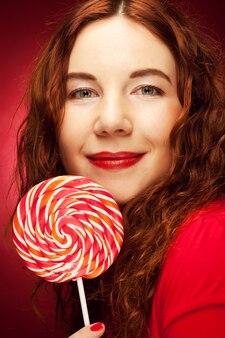 Bardzo młoda kobieta trzyma lolly pop.