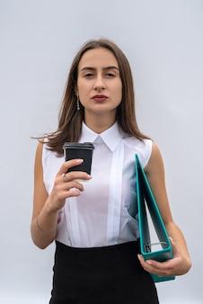 Bardzo młoda kobieta trzymać folder kubek nosić białą koszulę i czarną spódnicę na białym tle.
