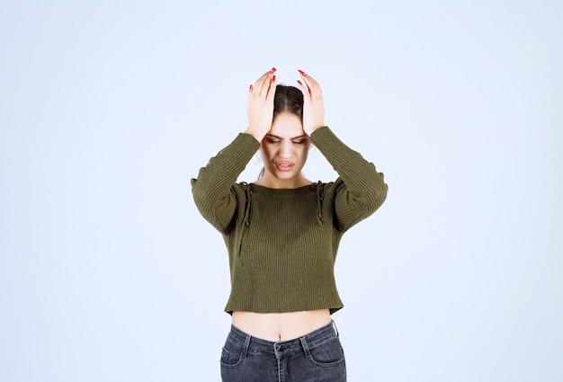 Bardzo młoda kobieta trzymając twarz na białej ścianie